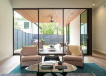 Dark-framed-glass-windows-connect-the-living-area-with-the-backyard-217x155