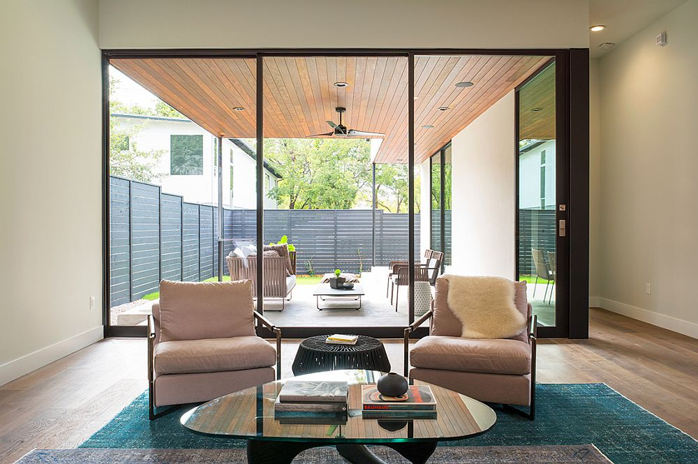 Dark, framed glass windows connect the living area with the backyard