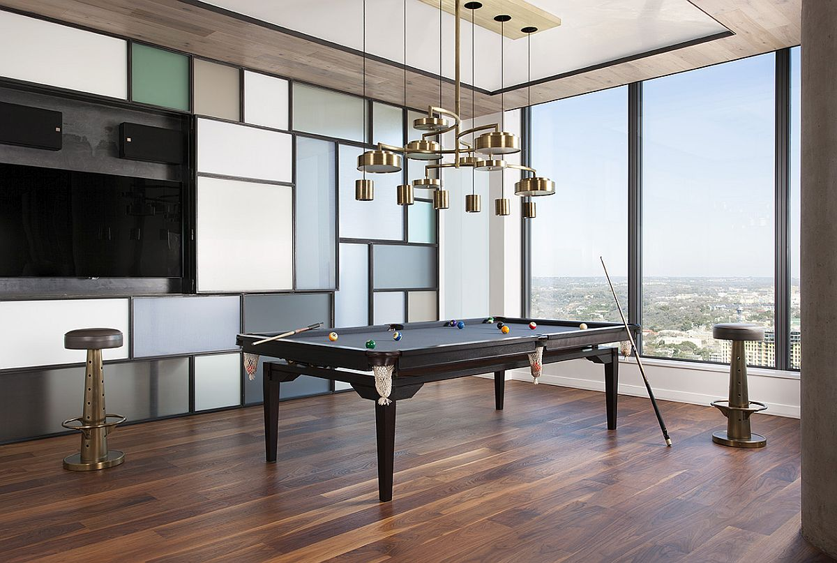 Dining table transformed into the pool table with chandelier above that also morphs