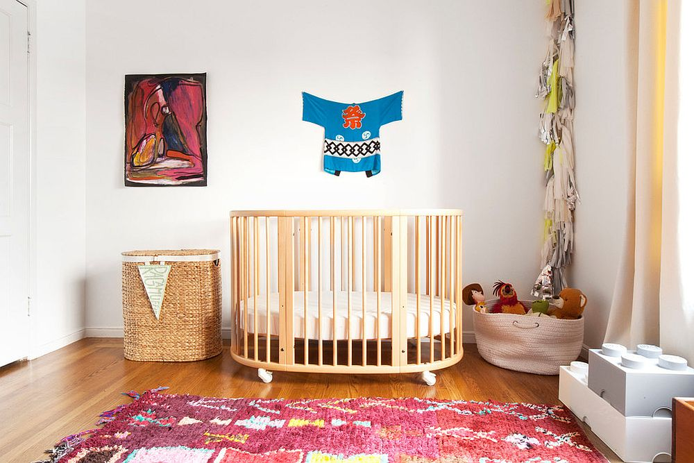 Eclectic nursery with crib on wheels and colorful rug in pink
