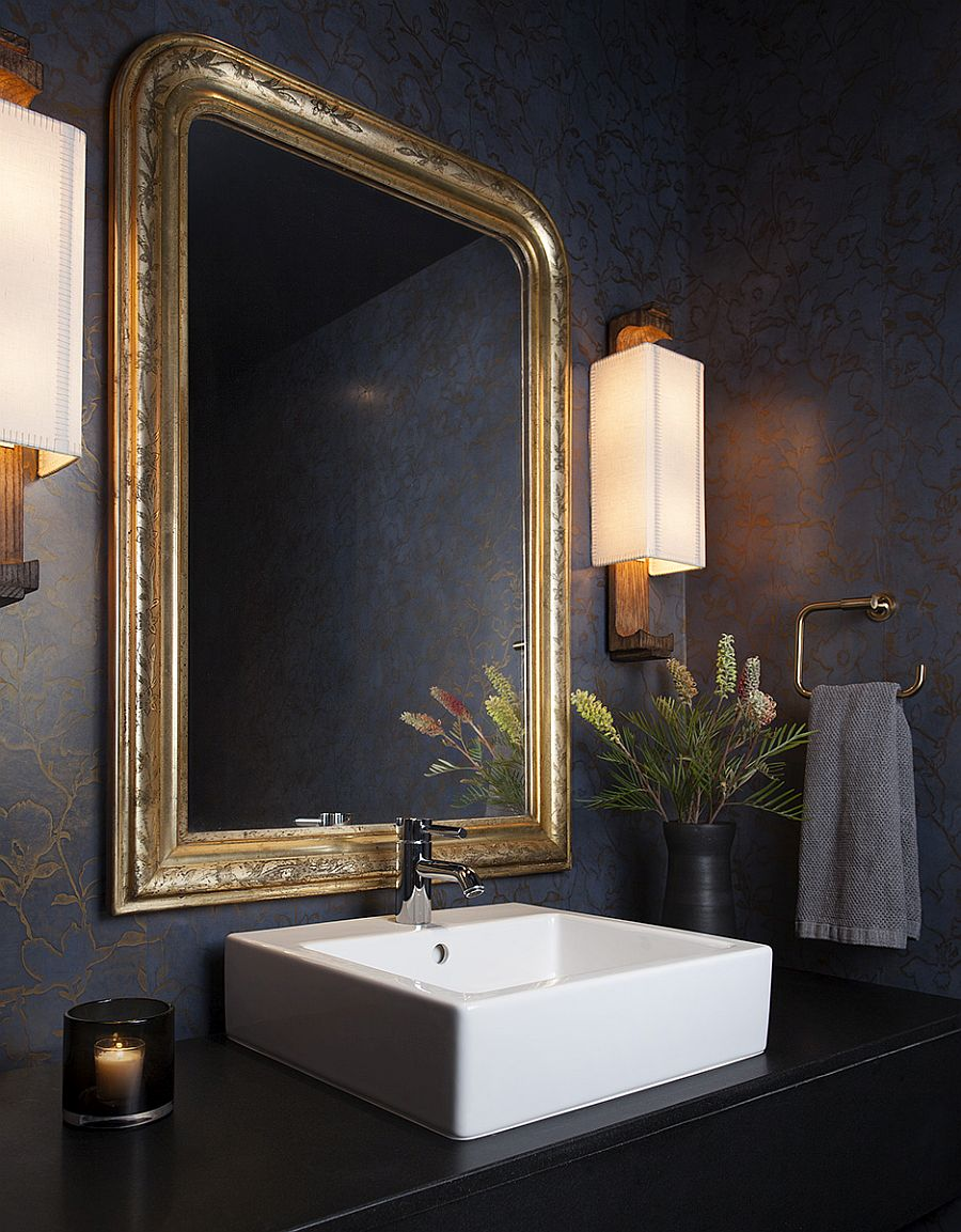 Golden glint of the mirror frame brings sparkle to the dark powder room