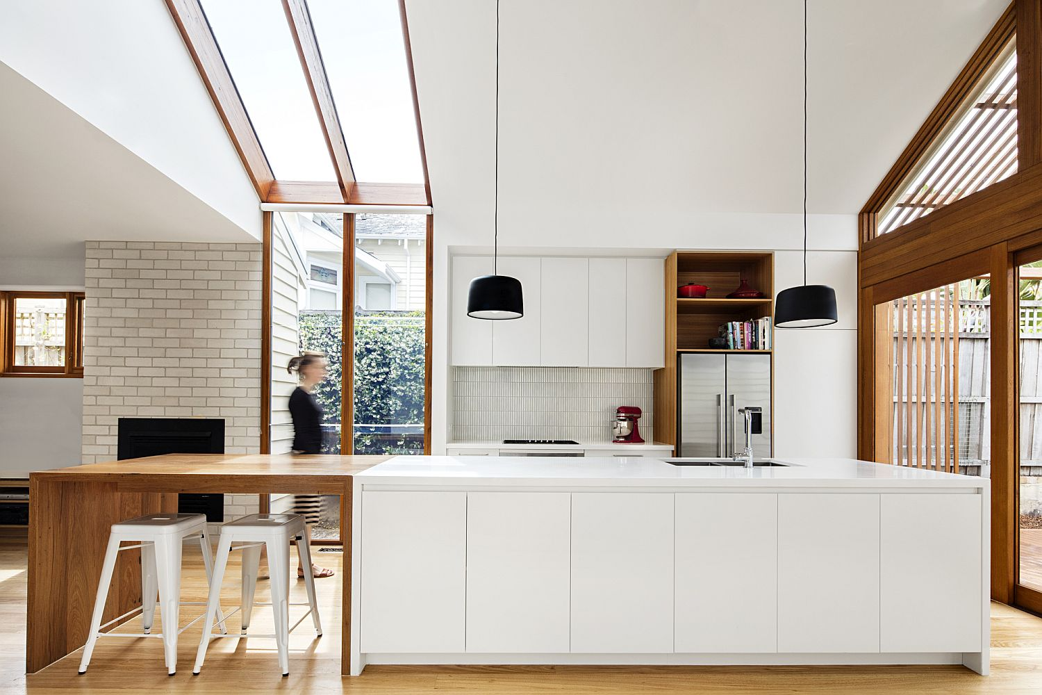 Modern kitchen in white with wooden cabinets and extended breakfast bench
