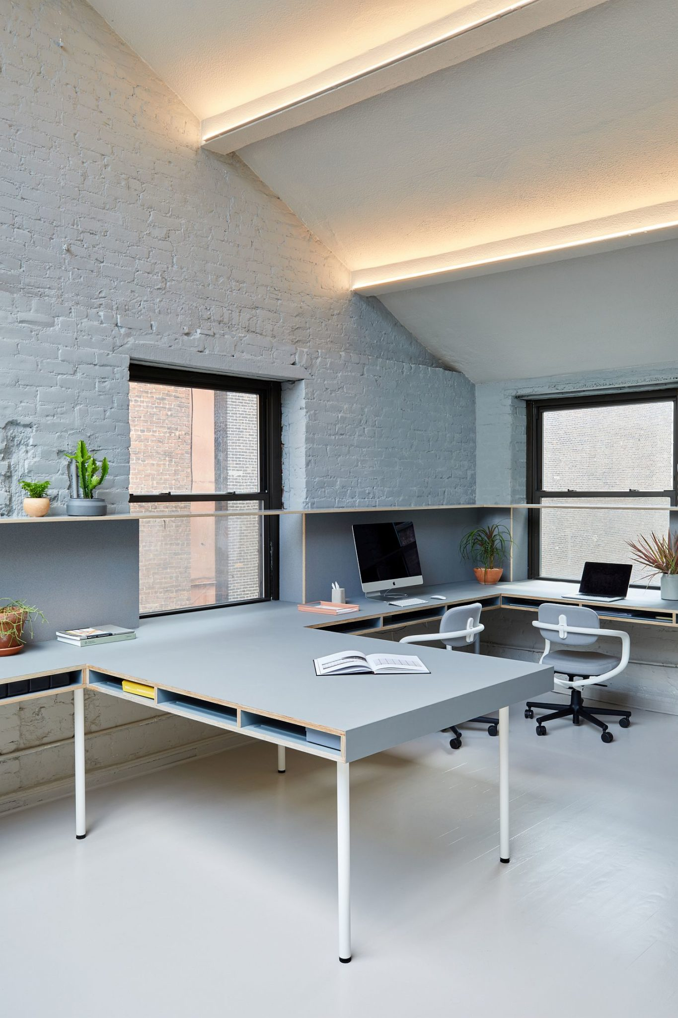 Smart lighting and sloped ceiling give the office a gorgeous look