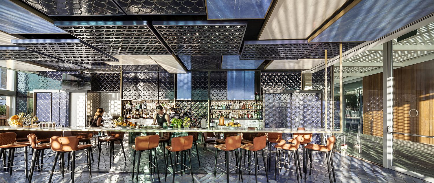 Stunning ceramic tiles ranging from navy blue to white shape a mesmerizing oceanside bar