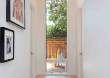 Walkway-with-framed-photos-inside-the-light-filled-Texas-home-217x155