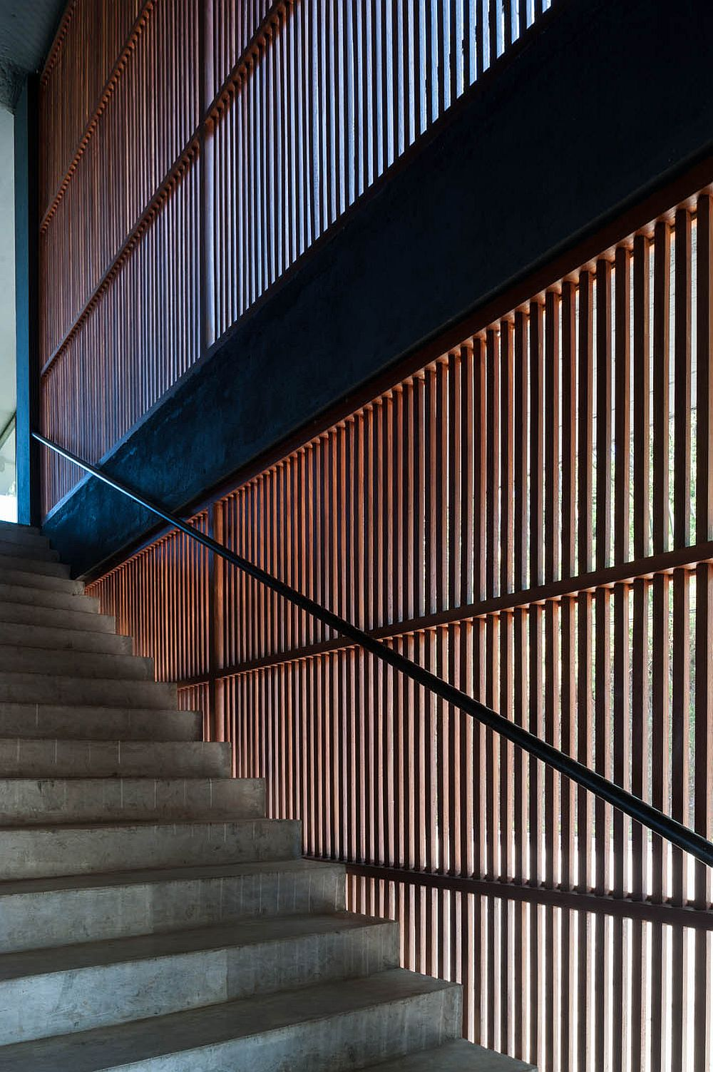 Wooden slats next to the stairs bring in ample natural light