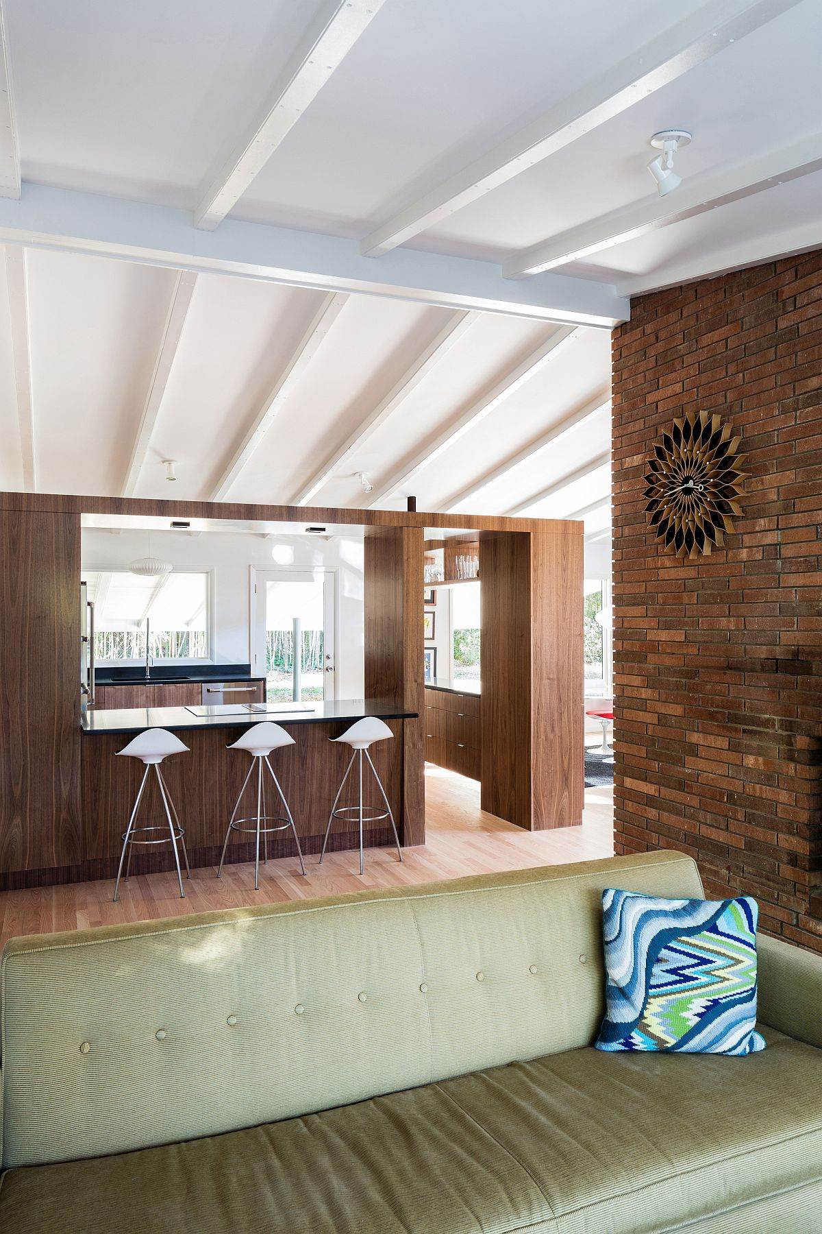 Wooden walls delineate the living area from the kitchen