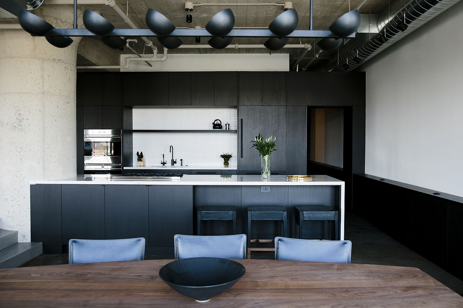 Fabulous kitchen in black with stunning lighting and an island in bluish-gray