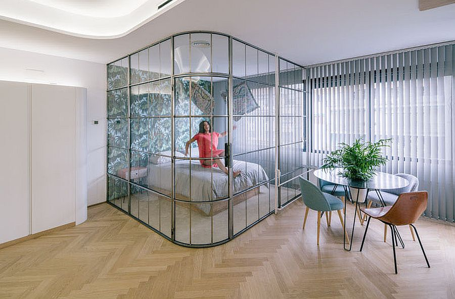 Glass walls delineate space in the small apartment without blocking light