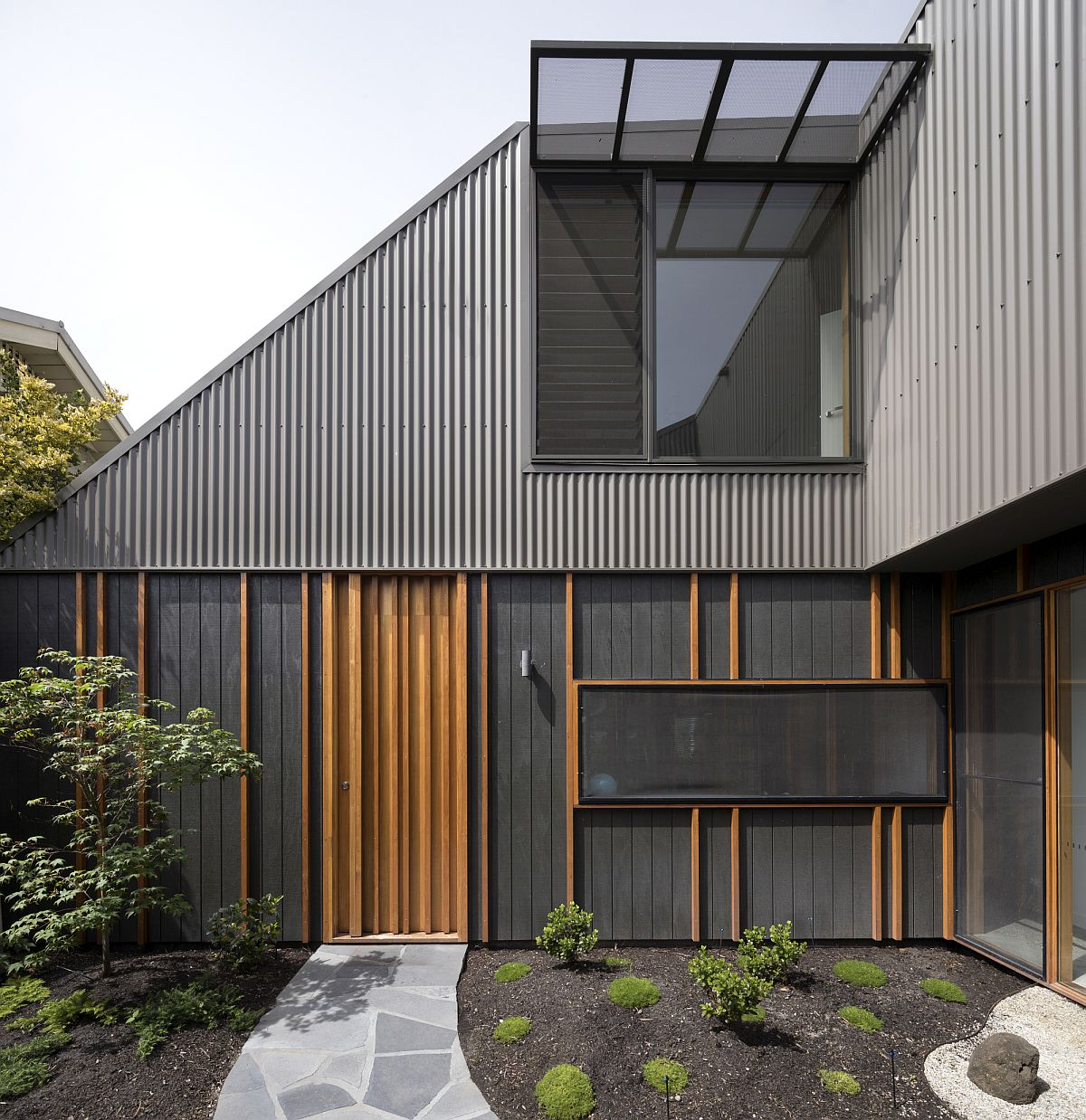 Gray exterior and curated courtyard of the low cost Aussie home