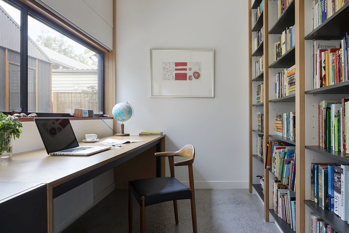 Light-filled home office with large bookshelf