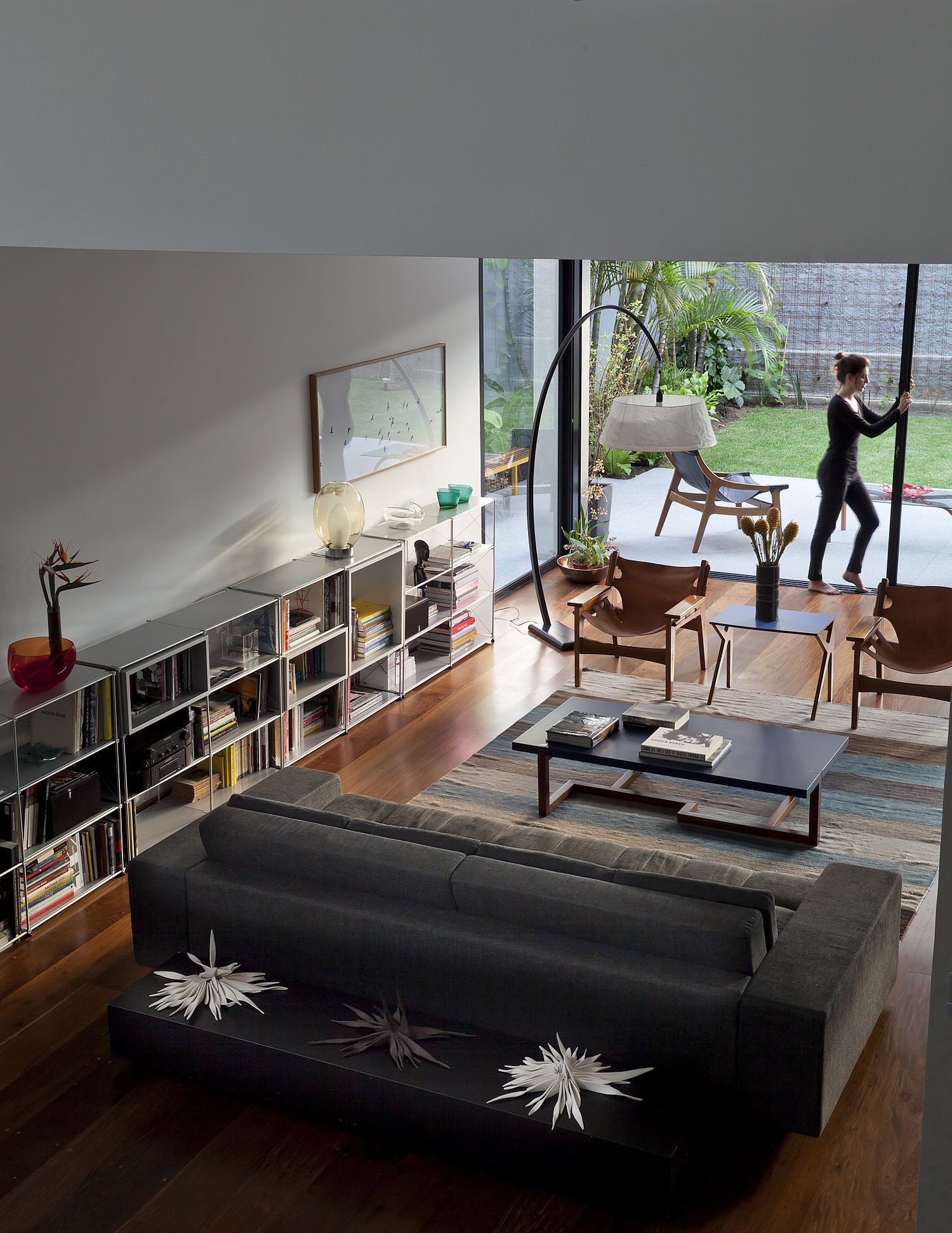 Living room of the Sao Paulo home with modern couch and space-savvy bookshelves