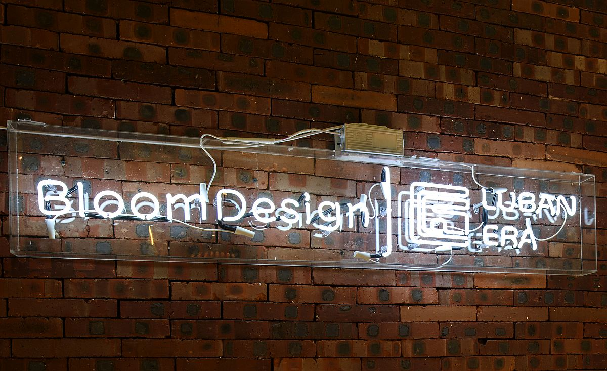 Logo-of-Bloom-Design-Studio-shines-bright-against-the-brick-wall-backdrop