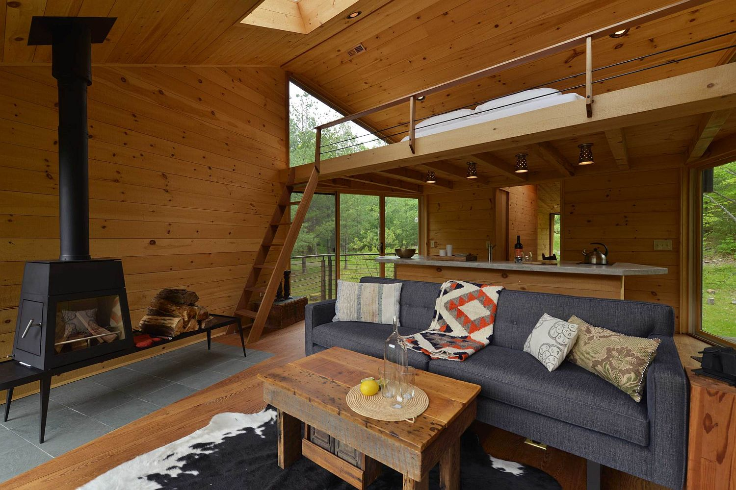 Lounge and loft level bedroom of the cabin in woods