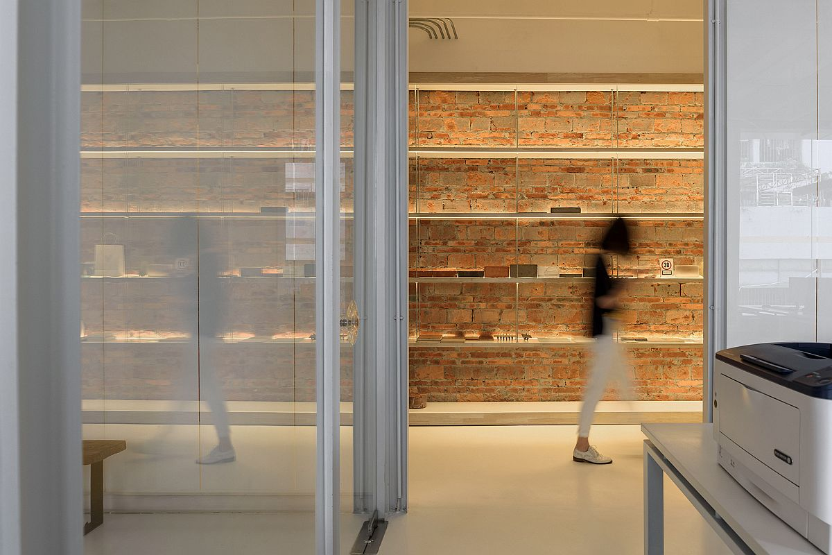 Red brick wall offers visual and textural contrast to an interior in white