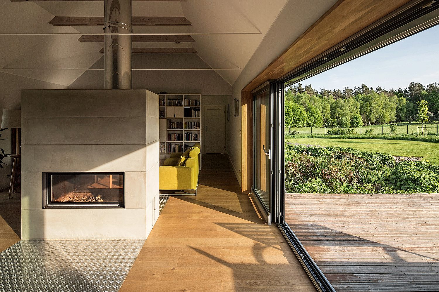 Sliding glass doors connect the living area and fireplace with the sunny deck outside