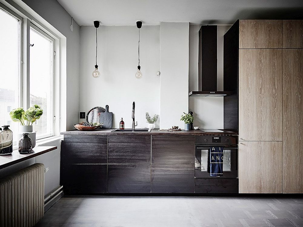 Small kitchen in the corner with different wood finishes