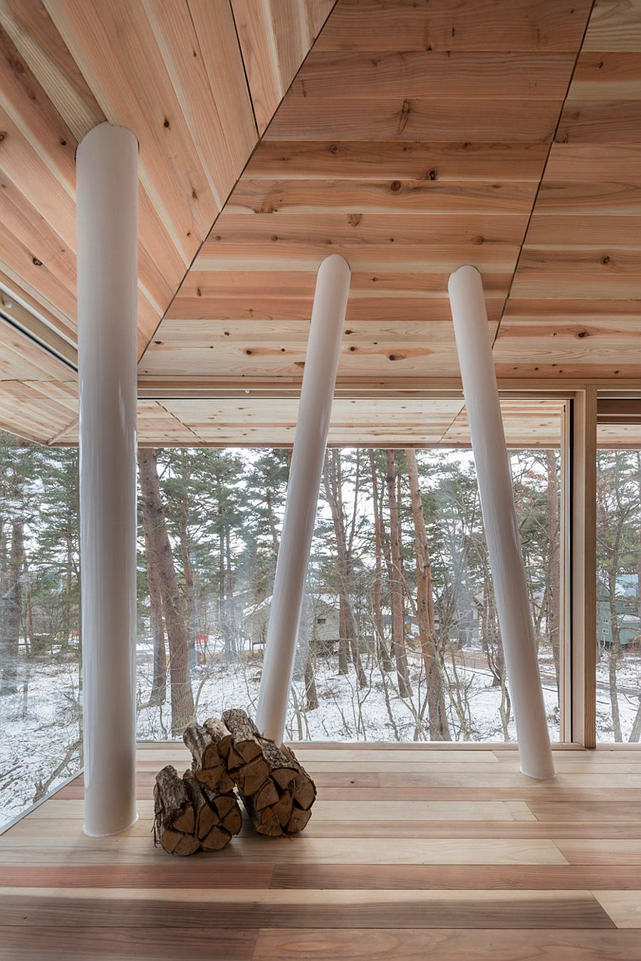 Supporting beams inside the One Year House draw inspiration from the trees outside