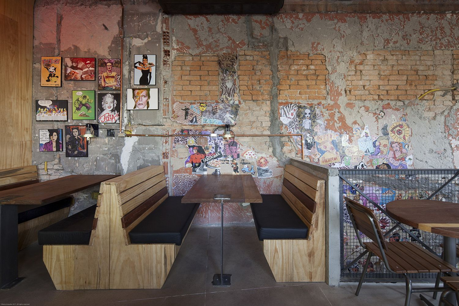 Weathered-walls-of-the-pizza-restaurant-with-framed-photographs-and-posters