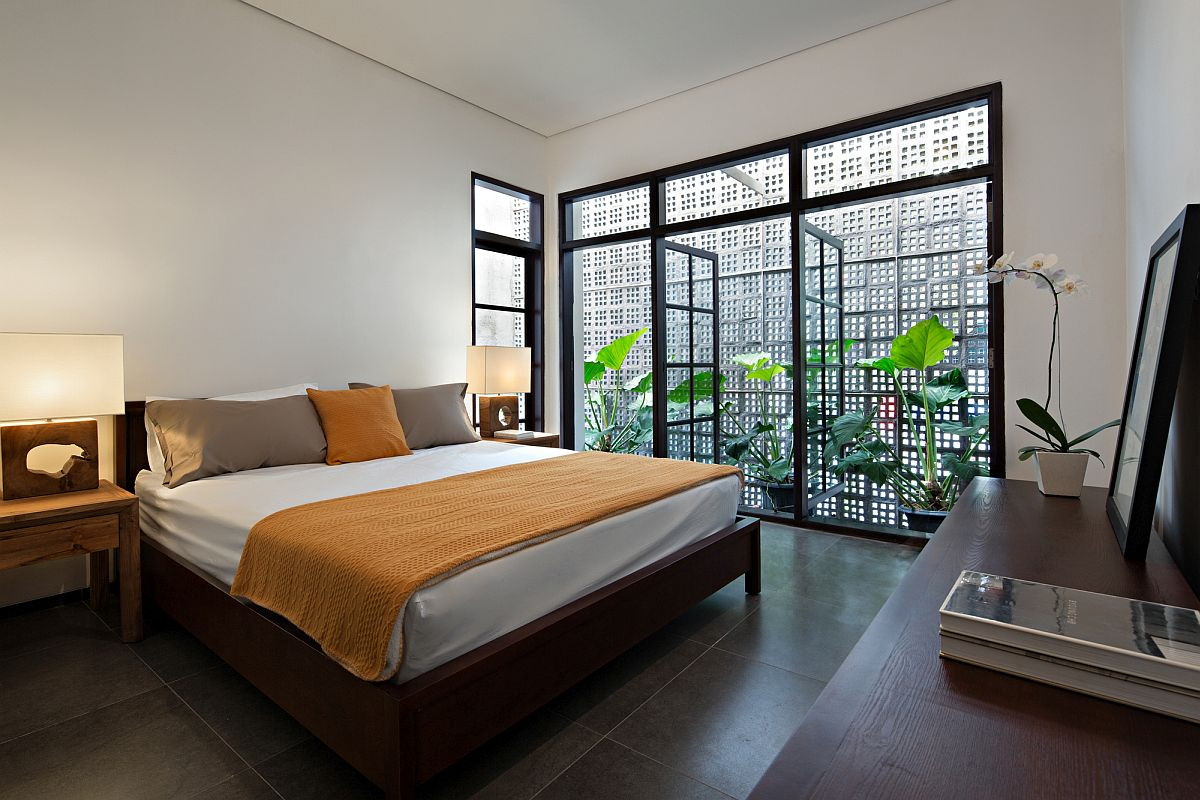 Bedroom with framed glass doors is filled with ample natural light