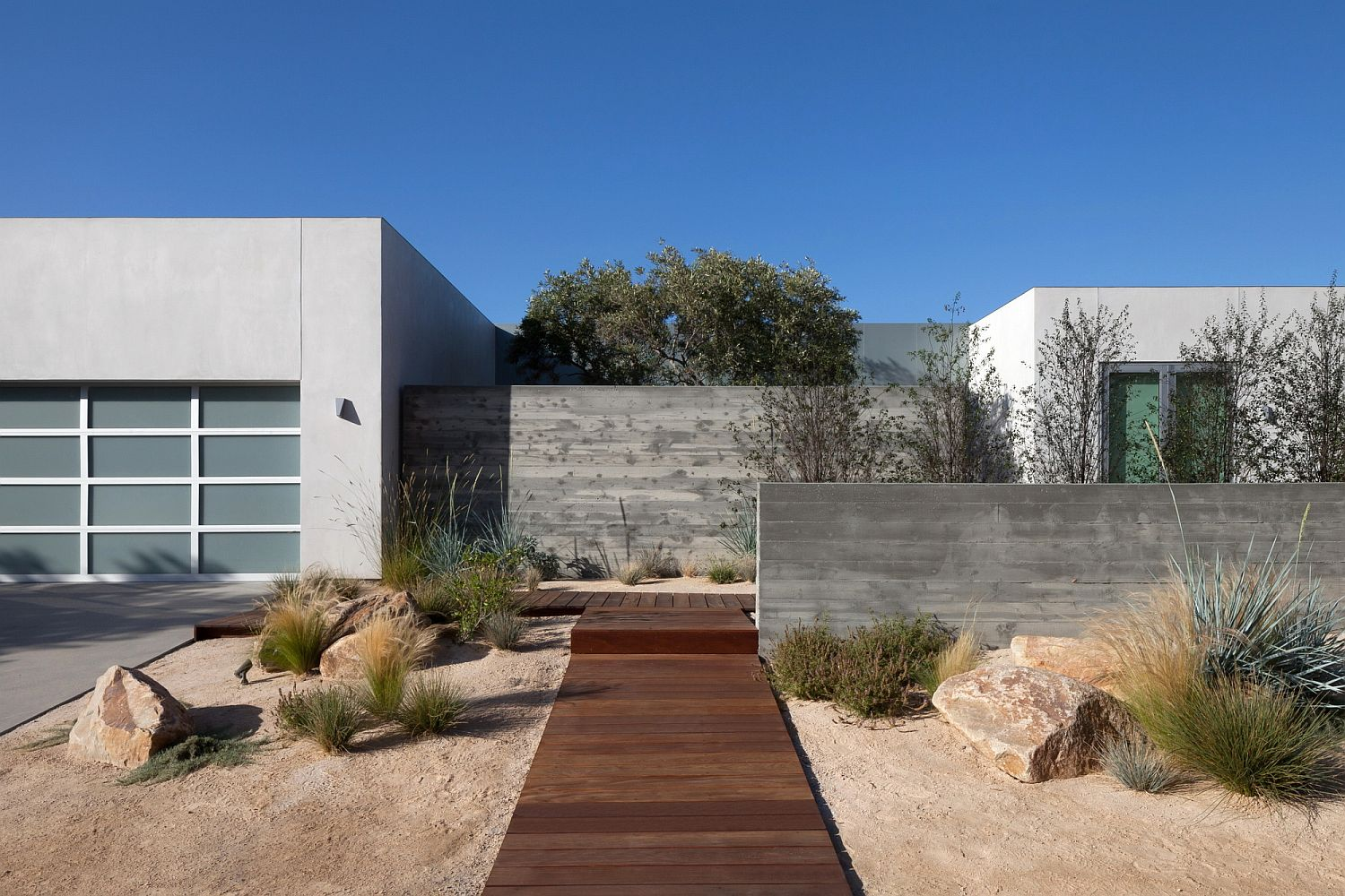 Curated front yard with a wooden walkway