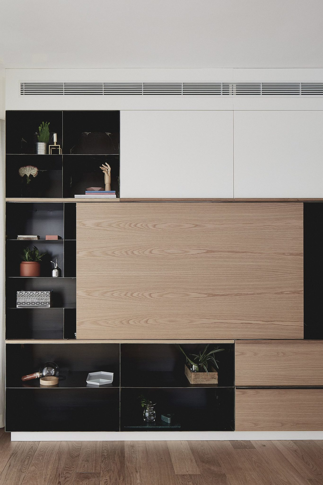 Dark cabinet with metallic elements and sliding wooden doors for the living room entertainment unit