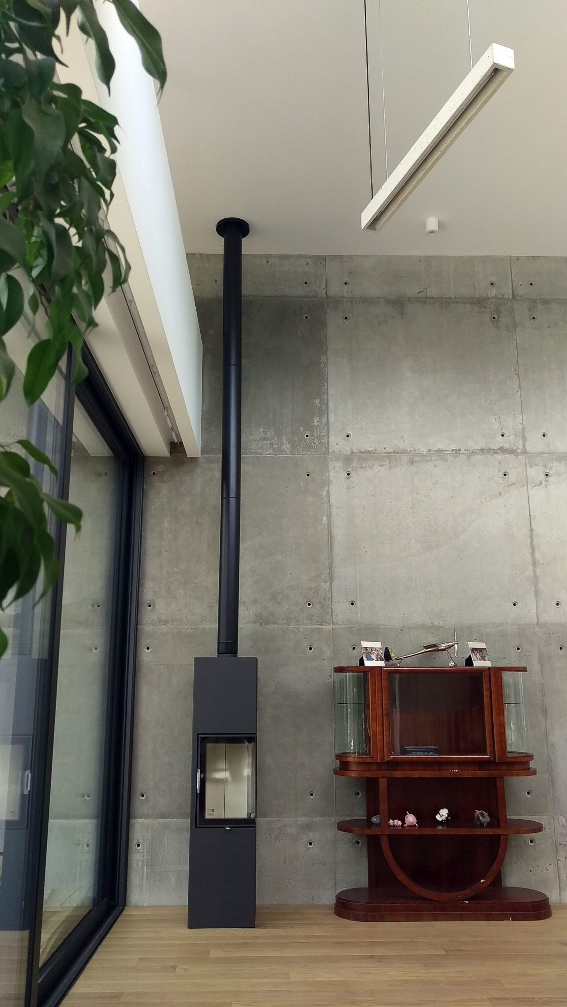 Fireplace-in-the-corner-next-to-the-accent-concrete-wall