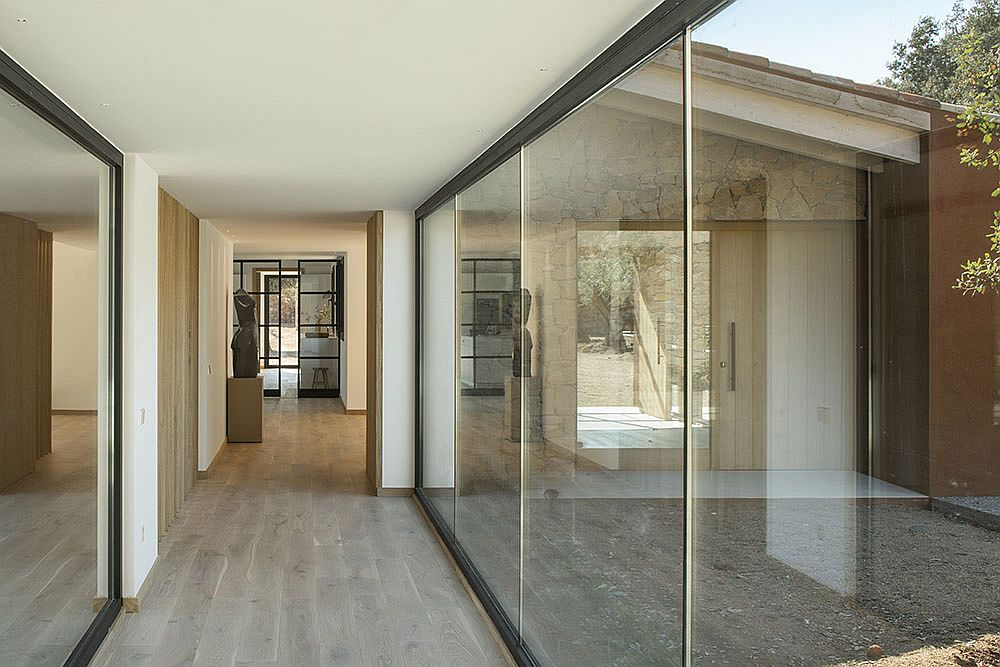 Floor-to-ceiling glass walls offer a view of the outdoors
