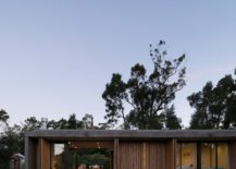 Folding-doors-with-wooden-slats-open-up-to-connect-the-interior-with-outdoors-217x155