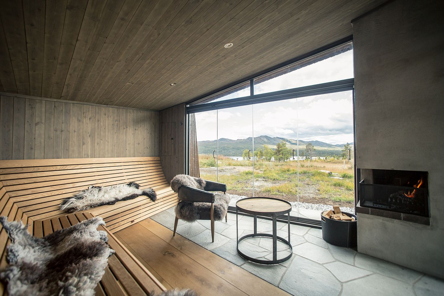 Interior of the cabin with lovely seating that offers a view of the landscape beyond