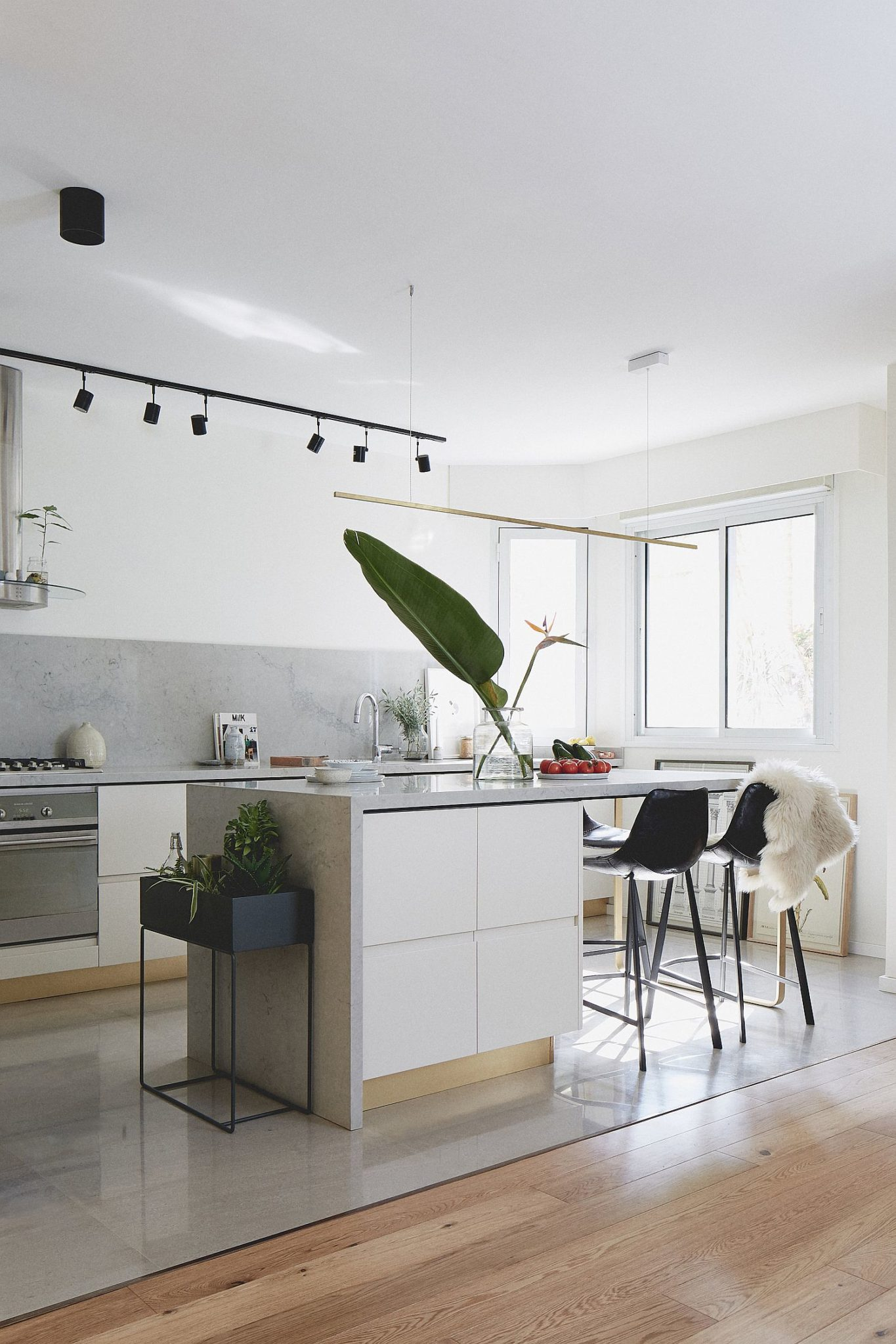 Light colored kitchen with marble, concrete and wooden surfaces