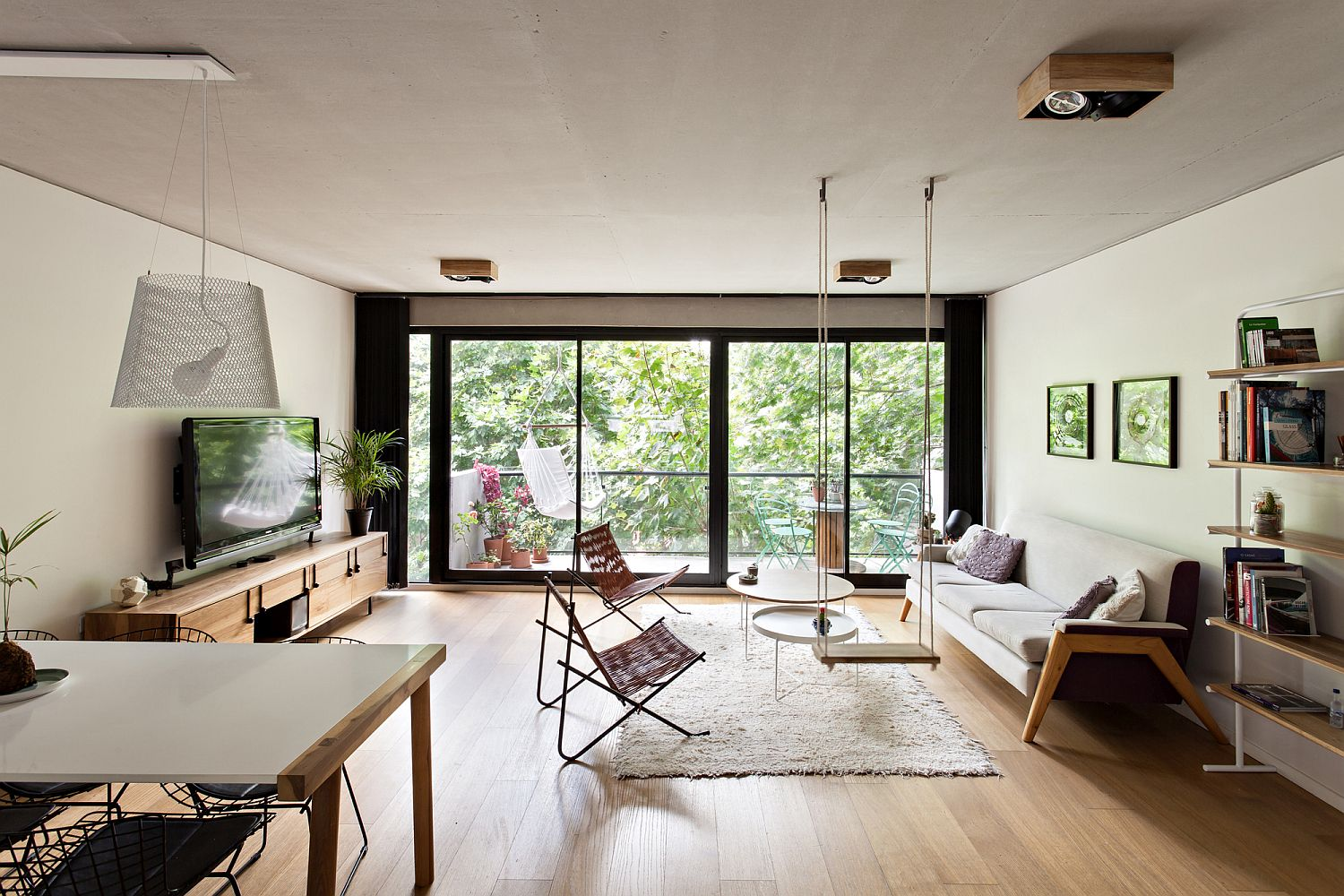 Living-room-with-multiple-seating-options-and-a-view-of-the-canopy-outdoors