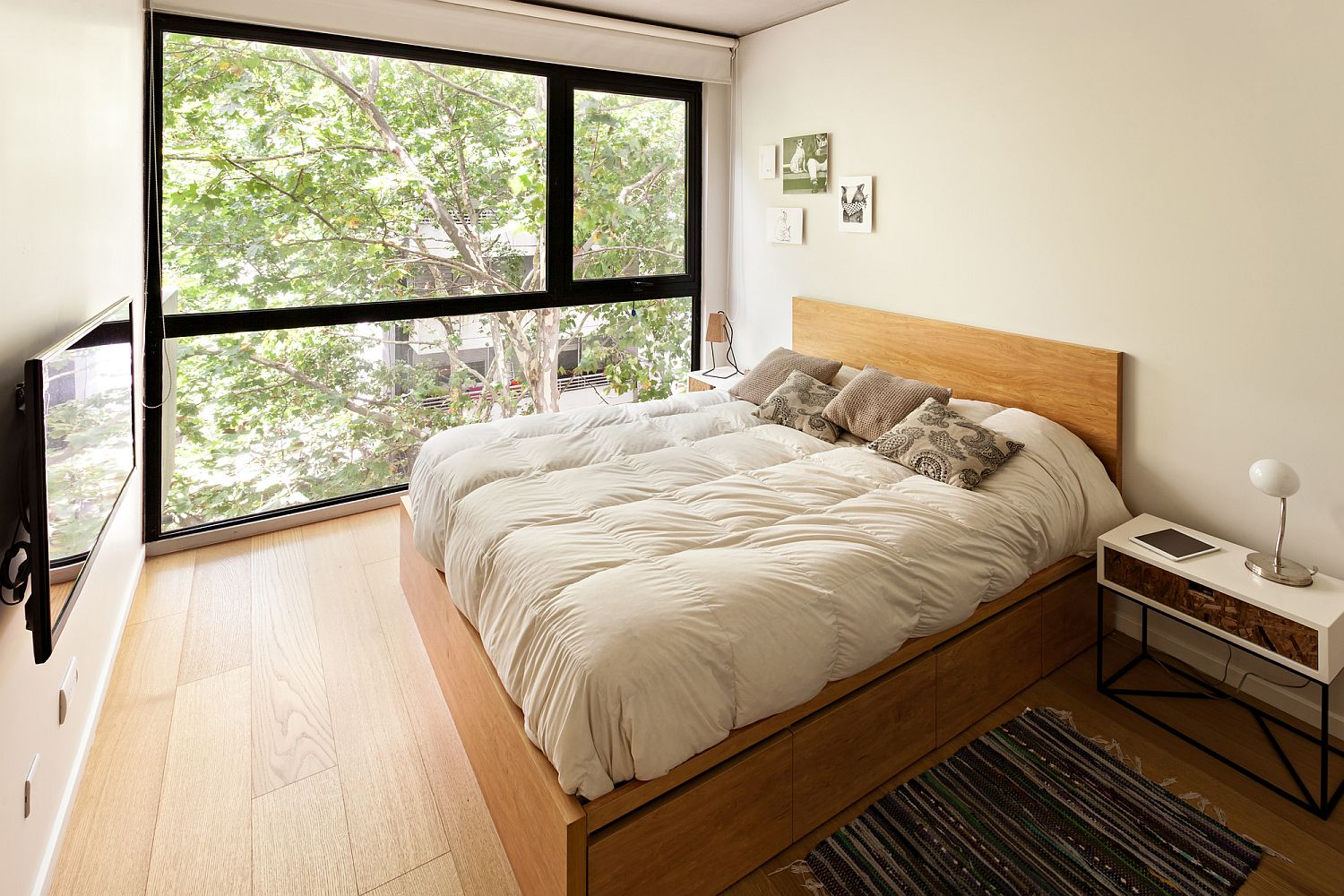 Modern-bedroom-in-white-with-wooden-flooring-and-a-space-savvy-bedside-table
