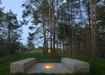 Outdoor-stone-benches-along-with-a-firepit-is-surrounded-by-the-evergreen-forest-217x155