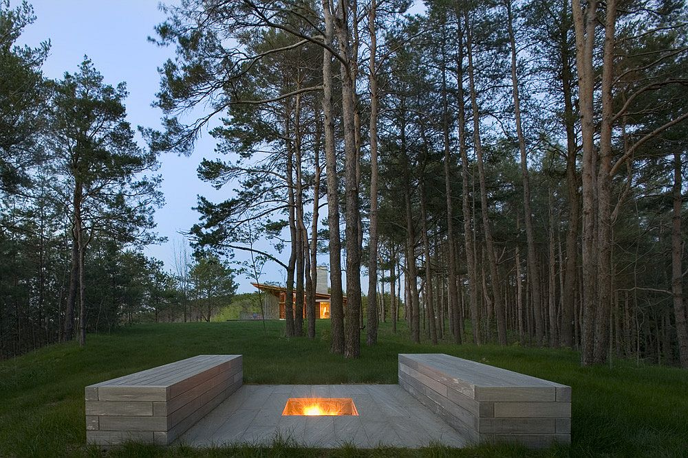 Outdoor-stone-benches-along-with-a-firepit-is-surrounded-by-the-evergreen-forest