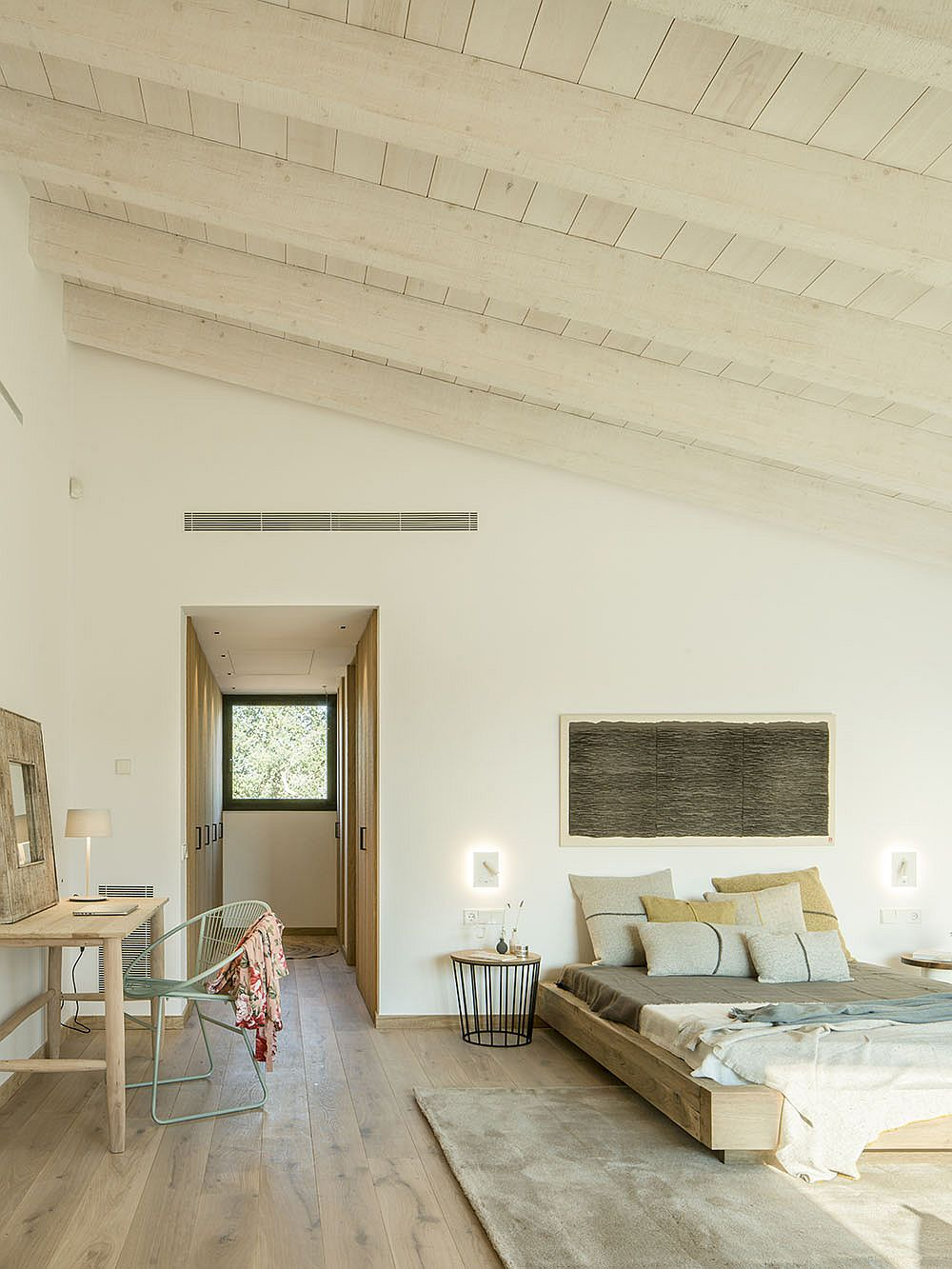 Sloped ceiling for the bedroom with wooden decor and a small workspace