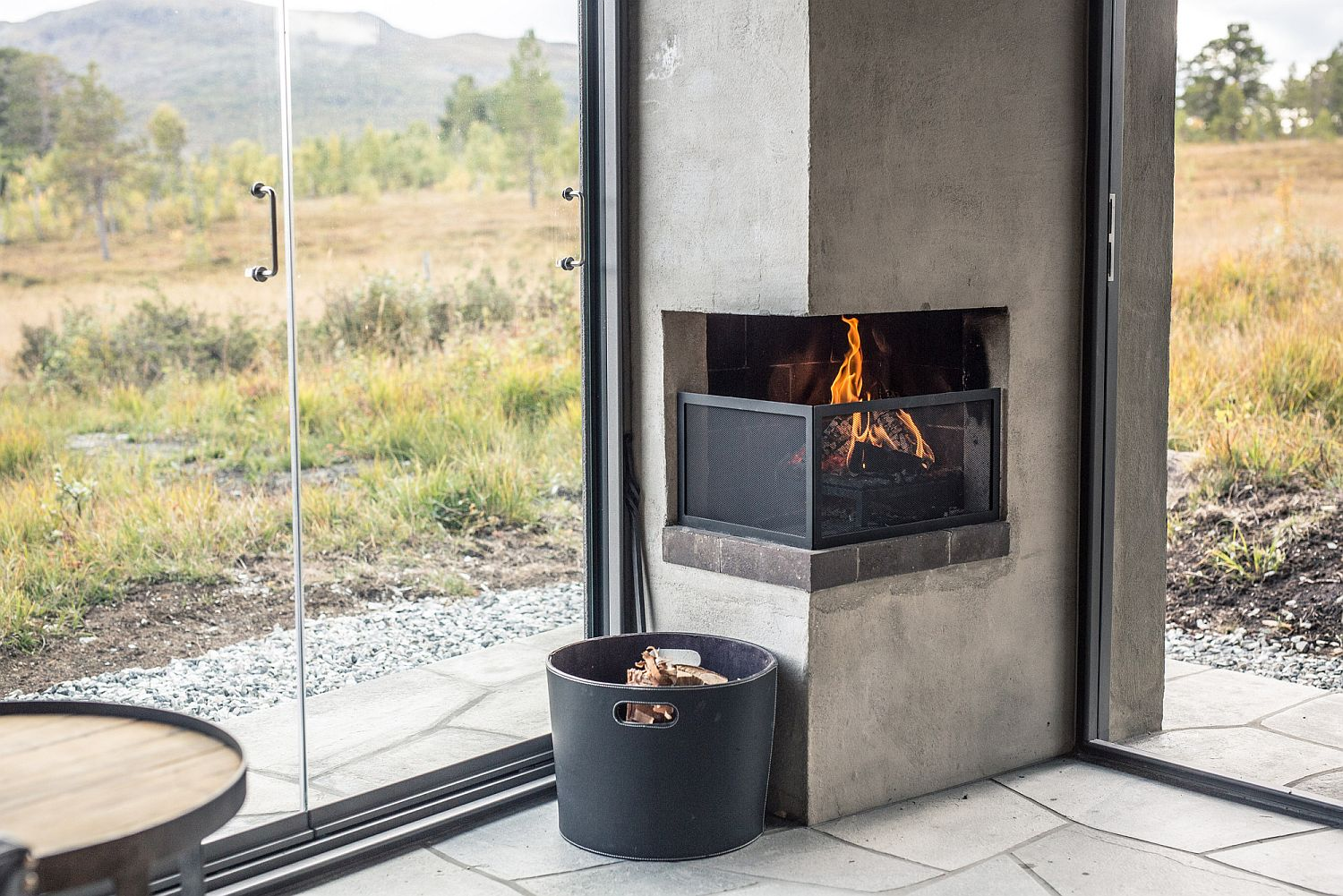 Small corner fireplace is built into the structure of the cabin
