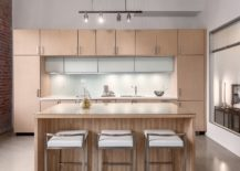 Spacious-and-light-filled-kitchen-with-brick-wall-on-one-side-and-wooden-cabinetry-217x155
