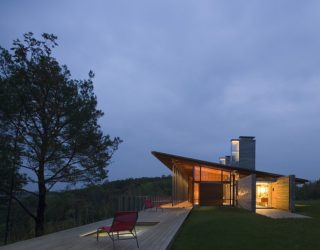 Cozy Minimal Retreat in Stone and Wood Engulfed in an Evergreen Forest