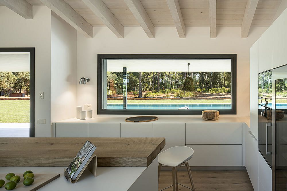 Window above the kitchen counter offers a view of the pool area