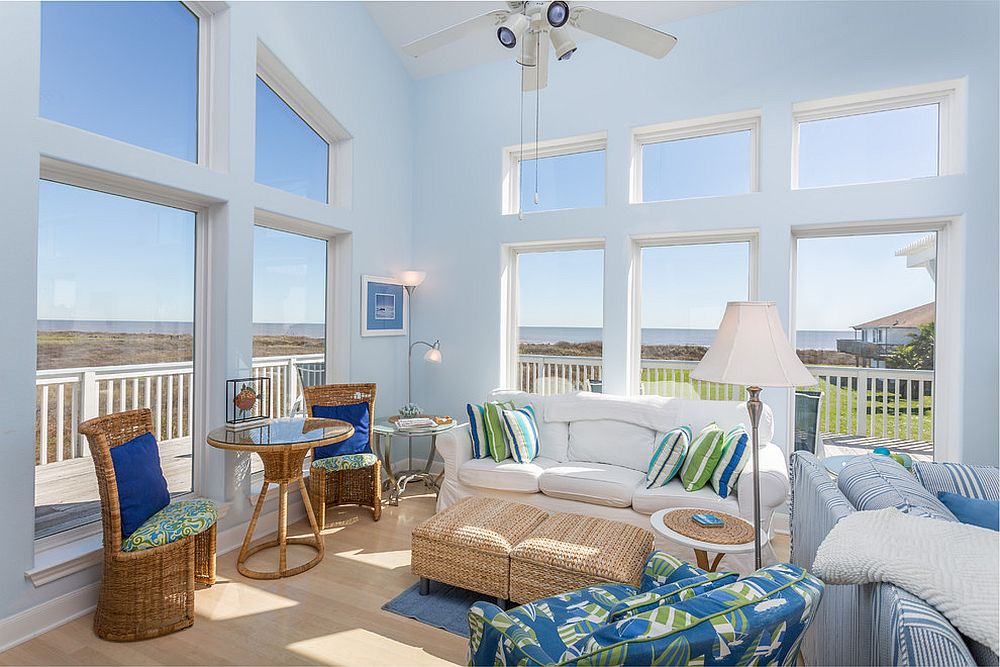 Light-filled beach style living room with decor made out of rattan and lovely blue accents