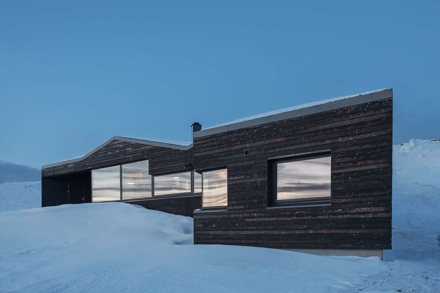 Minimal and striking exterior of the Norwegian cabin on snowy slopes