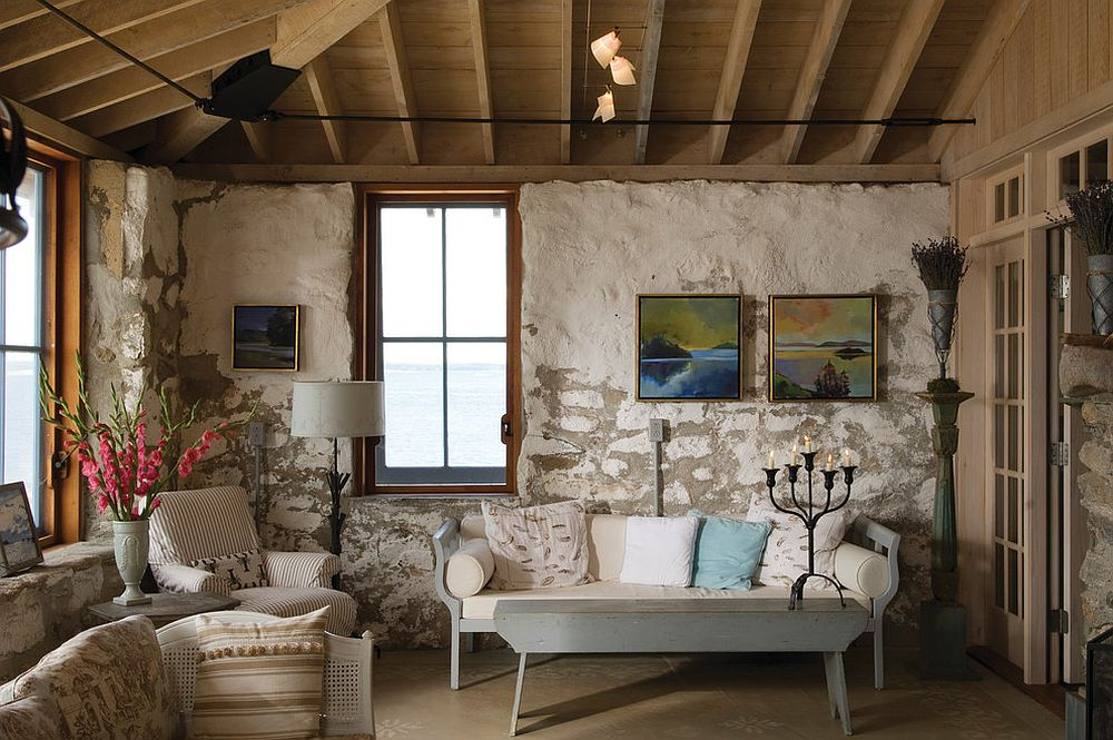Rustic approach to beach style living room design with exposed walls and wooden ceiling