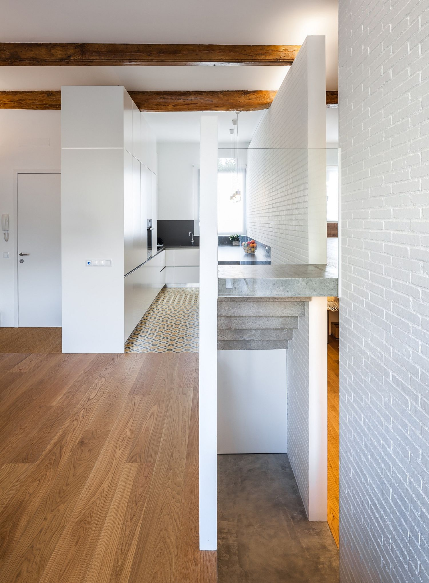 Small-corner-kitchen-in-white-with-wooden-flooring