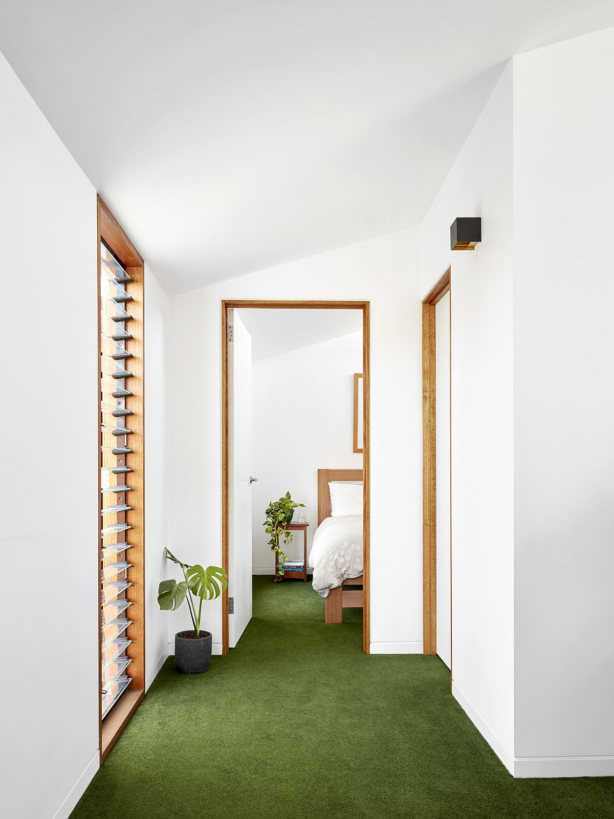 White and wood along with the green of the flooring creates a refreshing living environment