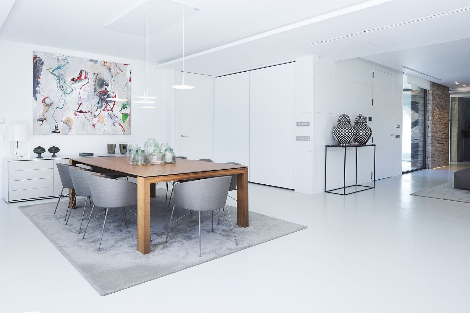 Contemporary dining room in white with a wooden table