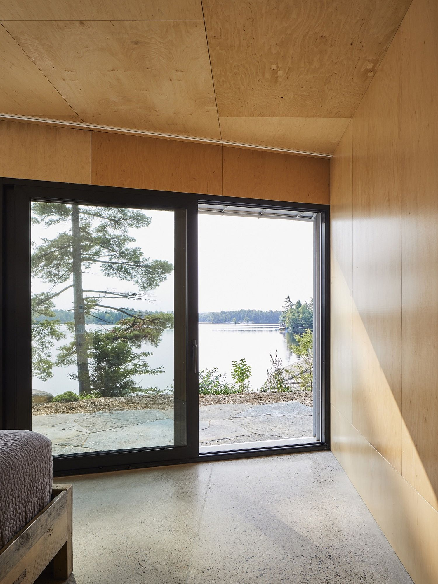Large glass doors connect the bedroom with a view of the lake outside