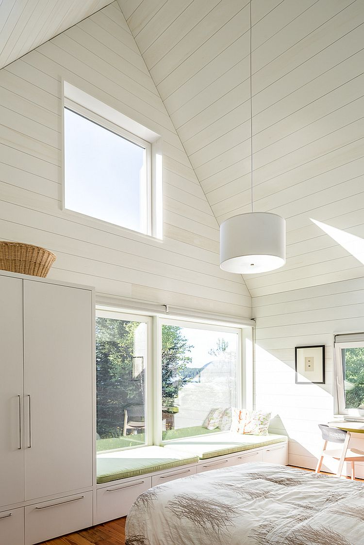 Light-filled bedroom of the house in white with a comfy window seat