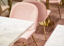 Marble-top-dining-tables-with-metallic-legs-and-pastel-pink-chairs-next-to-them-217x155