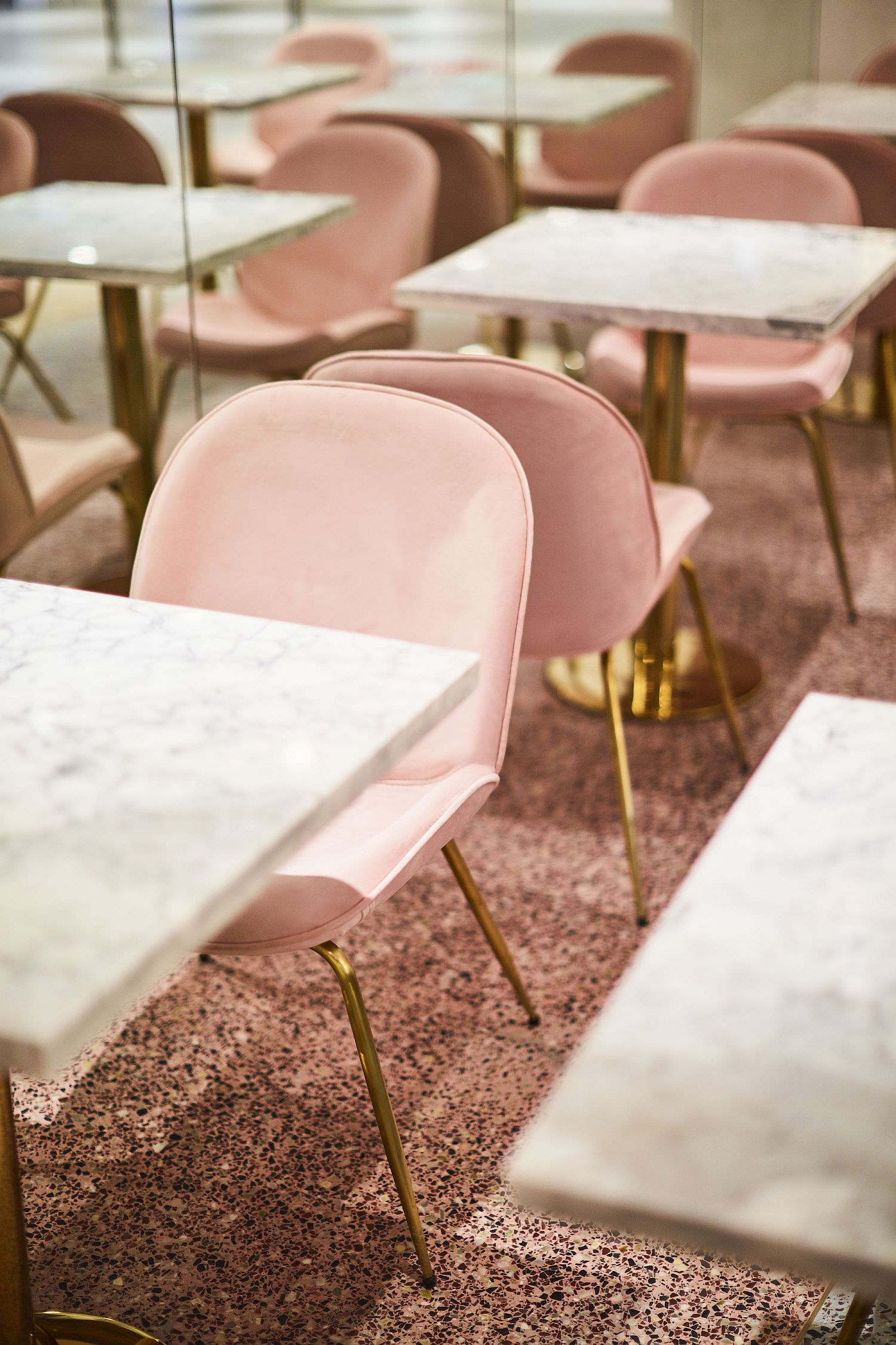 Marble top dining tables with metallic legs and pastel pink chairs next to them